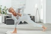 muž stojící ve obíhá boční úhel cvičení, Parivrtta Parsvakonasana pozice na jógu doma