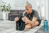 atletický muž v sportovní cvičení a strečink na jógu doma