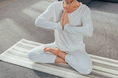cropped shot of man sitting in lotus position and meditating with namaste gesture on yoga mat
