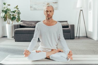 sporty adult man meditating in lotus position on yoga mat at home
