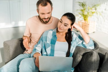 Handsome husband and beautiful wife sitting on couch and using laptop at home stock vector