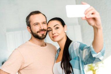 Loving couple taking selfie on smartphone stock vector