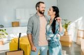 usmívající se pár všeobjímající a drží klíče od nového domu, stěhování koncept
