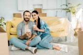kávét iszik, használ smartphone és pihenésre új ház, mozgó koncepció csomagolás után pár