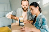 handsome husband and beautiful wife packing cardboard box with scotch tape, moving concept