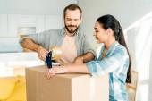 pohledný manžel a manželka balicí krabici lepící páskou, pohybující se koncept