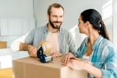 Mann und Frau Verpackung Karton mit Tesafilm, Umzug Konzept