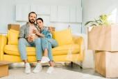 manžel a manželka sedí na gauči a pití kávy při balení pro nový dům, pohybující se koncept