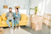 Fotografia concentrato coppia seduta sul divano, utilizzando il computer portatile e pianifica trasloco alla nuova casa, concetto commovente