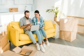 cílené pár sedí na gauči, pomocí přenosného počítače a plánování stěhování do nového domu, stěhování koncept