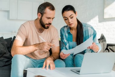 serious couple sitting on couch, filling papers, using laptop and planning