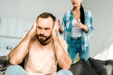 angry husband on foreground covering ears with hands and having argument with wife at home