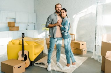 happy couple holding hands and embracing while packing for new house, moving concept
