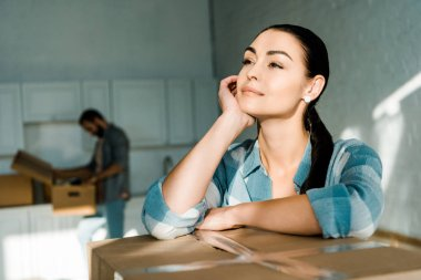 beautiful wife dreaming about new house with husband packing behind, moving concept