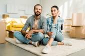 manžel a manželka sedí na podlaze a odpočinku po zabalení pro nový dům, pohybující se koncept