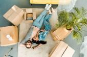 pohled shora páru leží na podlaze a relaxaci po zabalení pro nový dům, pohybující se koncept