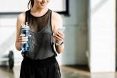 částečný pohled fit sportovkyně drží sportovní láhev s vodou a pomocí smartphone v tělocvičně