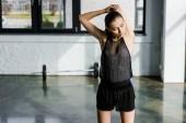 cílené sportovkyně dělá protahovací cvičení před trénink ve fitness studiu