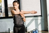 krásné sportovkyně dělá protahovací cvičení před trénink v tělocvičně