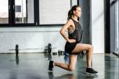 odhodlaný sportovkyně dělá lunge cvičení v tělocvičně