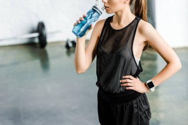 cropped view of fit sportswoman drinking water from sport bottle at gym