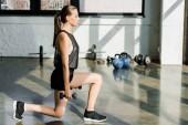 Fotografie attraktive sportliche Sportlerin Longe Übung mit Hanteln im Fitness-center