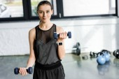 Fotografie determined smiling sportswoman training with dumbbells at gym