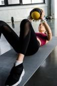 sportiva determinata sulla stuoia di forma fisica, allenamento con palla medica presso palestra