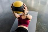 sportiva sulla stuoia di forma fisica, allenamento con palla medica presso palestra