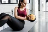 concentrata in forma sportiva lavorando abs con palla medica presso centro sportivo