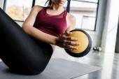 ritagliate la vista di sportiva lavorando abs con palla medica presso centro sportivo