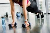 oříznutý pohled sportovkyně dělá push up s činkami v posilovně