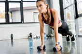 Fotografie schöne entschlossen Sportlerin tut Push Ups mit Hanteln im Fitness-Center