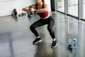 oříznutý pohled atletická sportovkyně dělat dřepy cvičení s činka ve fitness centru