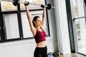 Fotografie krásná silná sportovkyně v vzpírání rukavice školení s činka v posilovně