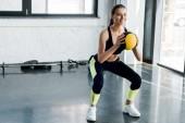sportswoman attraente facendo squat con palla medica presso palestra