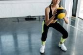 vista parziale di sportiva sorridente facendo squat con palla medica presso palestra