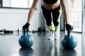 Photo cropped view of fit sportswoman in weightlifting gloves doing plank exercise on kettlebells at gym