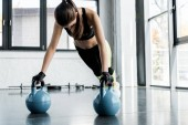 Photo strong sportswoman in weightlifting gloves doing plank exercise on kettlebells at gym
