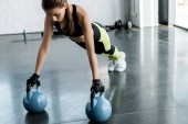 Photo focused fit sportswoman in weightlifting gloves doing plank exercise on kettlebells at gym