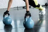 Photo cropped view of sportswoman in weightlifting gloves doing plank exercise on kettlebells at sports center