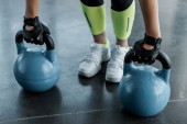 Photo low section of sportswoman in weightlifting gloves training with kettlebells at gym