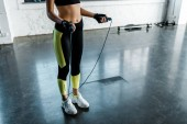 Fotografie cropped of sportswoman training with skipping rope at sports center