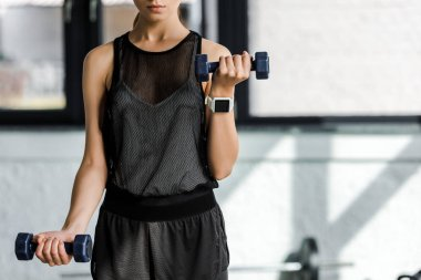 midsection of strong sportswoman training with dumbbells at fitness studio