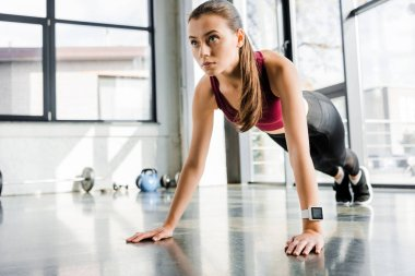 beautiful focused sportswoman doing push ups at fitness center