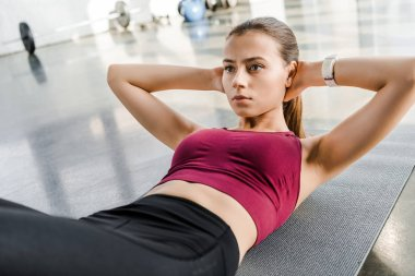 determined fit sportswoman doing abs exercise on fitness mat at sports center