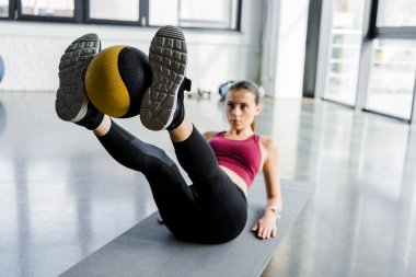 focused sportswoman on fitness mat training with medicine ball at gym