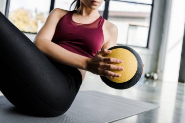 cropped view of sportswoman working out on abs with medicine ball at sports center