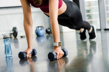 cropped view of sportswoman doing push ups with dumbbells at fitness center