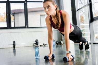 beautiful determined sportswoman doing push ups with dumbbells at fitness center